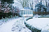 FORMAL TOWN GARDEN IN SNOW  OXFORD  WINTER: DESIGN BY LIZ NICHOLSON - LEAD ROOFED SUMMERHOUSE UNDERPLANTED WITH ROSE GERTRUDE JEKYLL AND HORNBEAMS  CARPINUS  BETULUS