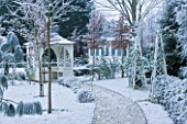 FORMAL TOWN GARDEN IN SNOW  OXFORD  WINTER: DESIGN BY LIZ NICHOLSON - ARBOUR/GAZEBO BY PATH WITH WOODEN OBELISKS  YEW HEDGING AND PINUS RADIATA