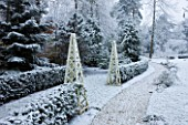 FORMAL TOWN GARDEN IN SNOW  OXFORD  WINTER: DESIGN BY LIZ NICHOLSON - PATH THROUGH GARDEN WITH WOODEN OBELISKS  YEW HEDGING  CERCIS SILIQUASTRUM AND CERCIDIPHYLLUM
