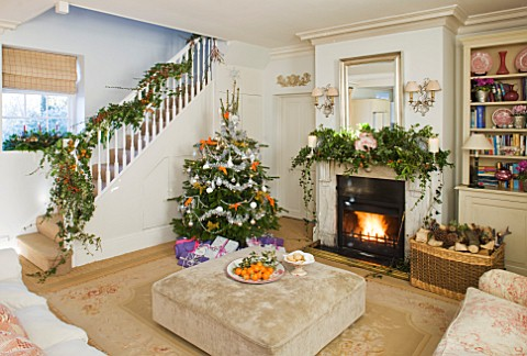 BRUERN_COTTAGES__OXFORDSHIRE_CHRISTMAS__THE_SITTING_ROOM_WITH_CHRISTMAS_TREE_SURROUNDED_BY_PRESENTS