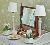 BRUERN COTTAGES  OXFORDSHIRE: CHRISTMAS - THE TWIN BEDROOM - TABLE WITH LAMPS  CYCLAMEN IN WHITE TEACUPS AND PLATE WITH MINCE PIES