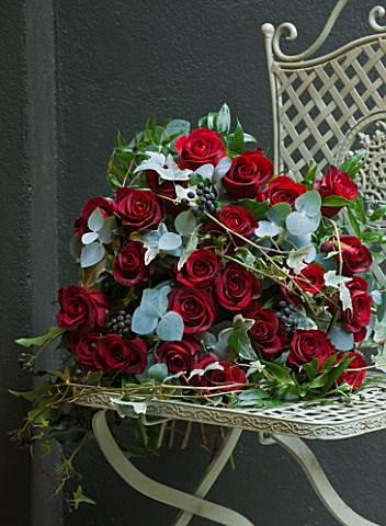 JUDITH_BLACKLOCK_VALENTINES_FLOWER_ARRANGEMENT_ON_METAL_CHAIR_WITH_ROSES__IVY_BERRIES_AND_EUCALYPTUS