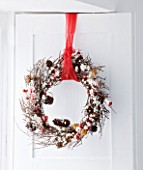 DESIGNER CAROLYN MINTY  GLOUCESTERSHIRE: TWIG WREATH WITH CONES AND BERRIES. CHRISTMAS