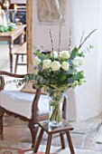 DESIGNER CAROLYN MINTY  GLOUCESTERSHIRE - VIEW THROUGH THE SITTING ROOM INTO THE DINING ROOM - VASE FILLED WITH ROSES  IVY  CATKINS AND EUCALYPTUS
