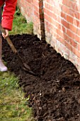 DESIGNER: CLARE MATTHEWS: PLANTING A BAREROOT RASPBERRY CANE FRUIT BUSH - PREPARING SOIL BED BY DIGGING WITH SPADE
