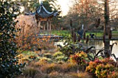 RHS GARDEN WISLEY  SURREY:  EVENING VIEW ACROSS THE LAKE AT SEVEN ACRES TO THE CHINESE PAGODA WITH HAMAMELIS APHRODITE  CAREX FLAGELLIFERA AND CAREX ASHIMENSIS EVERGOLD. WINTER