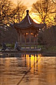 RHS GARDEN WISLEY  SURREY:  EVENING VIEW OF SEVEN ACRES ACROSS THE LAKE TO THE CHINESE PAGODA. WINTER  JANUARY