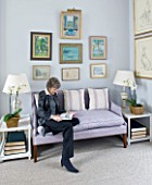 DESIGNER JANE CHURCHILL : THE DRAWING ROOM - JANE SITS ON A SOFA WITH SOME OF HER FAVOURITE PAINTINGS HUNG ABOVE