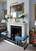DESIGNER JANE CHURCHILL : THE DRAWING ROOM - MODERN FIREPLACE WITH ANTIQUE FRENCH CLOCK  ANTIQUE SHOP MIRROR AND GLASS VASES FROM JANE CHURCHILLS GRANDMOTHER
