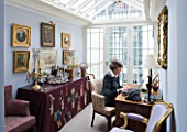 DESIGNER JANE CHURCHILL : JANE CHURCHILL SITS AT HER DESK IN THE CONSERVATORY WITH DRINKS TABLE