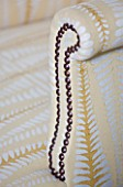 DESIGNER JANE CHURCHILL : STUD DETAIL ON ARM OF UPHOLSTERED CHAIR IN THE DRAWING ROOM
