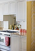 DESIGNER JANE CHURCHILL : THE KITCHEN SEEN FROM THE DINING ROOM - WHITE UNITS WITH HAND PAINTED TROMPE LOEIL BORDERS