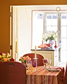 DESIGNER JANE CHURCHILL : THE DINING ROOM WITH KITCHEN BEYOND - YELLOW LINEN WALLS  CUSTOMISED CHAIRS WITH WEBBING AND STUDS ADDED  GLASSES BY IKEA AND WILLIAM YEOWARD