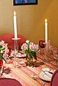 DESIGNER JANE CHURCHILL : THE DINING ROOM - MIXTURE OF IKEA AND WILLIAM YEOWARD GLASSES  VINTAGE PATTERNED DINNER PLATES. SILK TASSLE NAPKINS  CANDLES