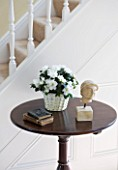 DESIGNER CLARE MATTHEWS - HOUSEPLANT PROJECT - WHITE AZALEA IN A WICKER CONTAINER ON A TABLE IN HALLWAY BESIDE STAIRS
