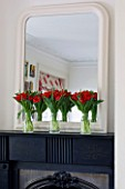DESIGNER: KALLY ELLIS  LONDON: ALADDIN TULIPS IN GLASS VASE ALONG MANTELSHELF OF FIREPLACE IN MAIN BEDROOM. MIRROR