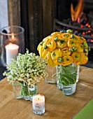 DESIGNER: KALLY ELLIS  LONDON: GLASS VASES HOLD LILY-OF-THE-VALLEY AND RANUNCULUS BLOOMS; FRAGRANT MCQUEENS CANDLE. FIRE IN BACKGROUND