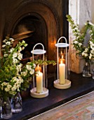 DESIGNER: KALLY ELLIS  LONDON: HURRICANE LAMPS AND GLASS JARS OF SPIRAEA DECORATE THE HEARTH