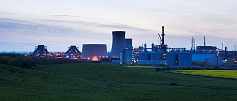 TEESSIDE__UNITED_KINGDOM__PETROCHEMICAL_WORKS_AT_DUSK_SEEN_FROM_FIELD_OF_RAPESEED__INDUSTRY__OIL_IND