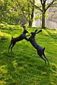 CERNEY HOUSE GARDEN  GLOUCESTERSHIRE: SCULPTURE OF BOXING HARES BY MIRANDA MICHELS