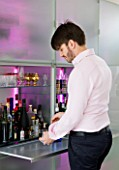 CAKE BOY HOUSE  LONDON: ERIC LANLARD MAKING DRINKS ON THE SLIDE- OUT PANEL OF THE LED LIT FROSTED GLASS STORAGE CABINET BY EO  IN THE LIVING ROOM