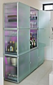 CAKE BOY HOUSE  LONDON: FROSTED GLASS STORAGE CABINET WITH LED COLOUR CHANGER AND SLIDE OUT PANEL FOR DRINKS  BY EO  IN THE LIVING ROOM