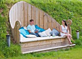 DESIGNER CLARE MATTHEWS - DECKING PROJECT - THE THRONE - DECK SEAT SET INTO HILLSIDE WITH BLUE AND WHITE CUSHIONS