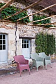 PRIEURE NOTRE-DAME DORSAN  FRANCE: VITIS COIGNETIAE TRAINED AGAINST THE STONE WALLS OF THE PRIORY WITH CHAIRS IN FRONT