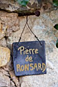 PRIEURE NOTRE-DAME DORSAN  FRANCE: ROSE  PLANT LABEL ON WALL FOR ROSA PIERRE DE RONSARD