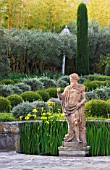 DESIGNER MICHEL SEMINI  PROVENCE  FRANCE: MAS THEO - THE SWIMMING POOL GARDEN WITH STATUE OF NEPTUNE  IRISES AND PARTERRE OF CLIPPED TEUCRIUM FRUTICANS AND SANTOLINA