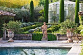 DESIGNER MICHEL SEMINI  PROVENCE  FRANCE: MAS THEO - THE SWIMMING POOL GARDEN WITH STATUE OF NEPTUNE  IRISES AND PARTERRE OF CLIPPED TEUCRIUM FRUTICANS AND SANTOLINA - GREENHOUSE