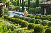 DESIGNER MICHEL SEMINI  PROVENCE  FRANCE: MAS THEO - THE SWIMMING POOL GARDEN WITH STATUE OF NEPTUNE AND PARTERRE OF CLIPPED TEUCRIUM FRUTICANS AND SANTOLINA
