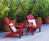 DESIGNER DOMINIQUE LAFOURCADE  PROVENCE  FRANCE: MODERN CONTEMPORARY GARDEN - DECKING TERRACE WITH RED WOODEN CHAIRS