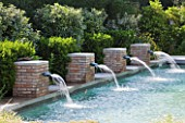 DESIGNER DOMINIQUE LAFOURCADE  PROVENCE  FRANCE: SWIMMING POOL WITH FOUR SQUARE BRICK FOUNTAINS THAT SPURT RE-CYCLED WATER BACK INTO SWIMMING POOL