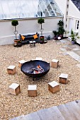 DESIGNER: CLARE MATTHEWS  DEVON - PAVING PROJECT - GRAVEL SEATING AREA WITH LARGE SQUARE WOODEN BLOCKS FOR SEATS AND FIRE CAULDRON