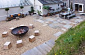 DESIGNER: CLARE MATTHEWS  DEVON - PAVING PROJECT - PATIO WITH TABLE AND CHAIRS AND GRAVEL SEATING AREA WITH LARGE SQUARE WOODEN BLOCKS FOR SEATS AND FIRE CAULDRON