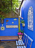 KARLA NEWELL GARDEN  BRIGHTON: SMALL TOWN GARDEN - COURTYARD WITH BLUE WALL PAINTED WITH POWDER PIGMENT  WOODEN BENCHES AND WOODEN PERGOLA