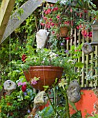 KARLA NEWELL GARDEN  BRIGHTON: SMALL TOWN GARDEN - ORANGE WALL  HANGING BASKETS AND STONES GATHERED FROM THE BEACH