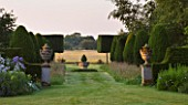 KINGSBRIDGE FARM  BUCKINGHAMSHIRE: FORMAL YEW AVENUE WITH MEADOW GRASS AND CENTRAL FONT AND PLEACHED HORNBEAM  FARMLAND BEYOND