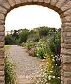 WHATLEY MANOR  WILTSHIRE: HERBACEOUS BORDER SEEN THROUGH ARCHWAY FROM THE KITCHEN GARDEN