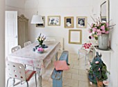 AMANDA KNOX HOUSE  GRANTHAM: THE DINING ROOM - WHITE WITH HINTS OF PINK - TABLE WITH OILCLOTH TABLECLOTH  CHAIRS FROM IKEA   FADED BLUE WOODEN BENCH  FAMILY PORTRAITS IN OLD FRAMES