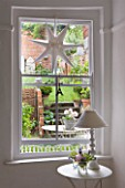 AMANDA KNOX HOUSE  GRANTHAM: THE DINING ROOM - WHITE WITH HINTS OF PINK - LARGE SASH WINDOW LOOKING OUT INTO COURTYARD. TABLE WITH LAMP  STAR DECORATION IN WINDOW