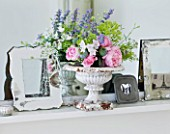 AMANDA KNOX HOUSE  GRANTHAM: THE WHITE SITTING ROOM - MANTELPIECE ABOVE FIREPLACE WITH PHOTO FRAMES  A VINTAGE WHITE METAL GARDEN URN WITH FRESH FLOWERS