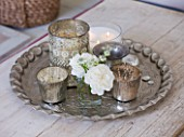 AMANDA KNOX HOUSE  GRANTHAM: THE WHITE SITTING ROOM - SILVER TEA LIGHT HOLDERS  CANDLES AND GLASS VASES ON A PATTERNED VINTAGE SILVER TRAY AS A COFFEE TABLE CENTRE PIECE