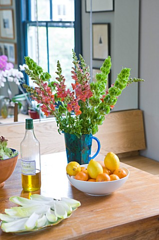CHANTAL_COADY_HOUSE__LONDON_THE_DINING_ROOM_WITH_MIRRORED_CUPBOARDS_BEHIND__SNAPDRAGONS_IN_VASE__BAL