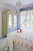 DESIGNER JACKY HOBBS  LONDON - WHITE BEDROOM AT CHRISTMAS WITH PRESENT ON BED AND BEAUTIFUL WARDROBE WITH MIRRORED FRONT