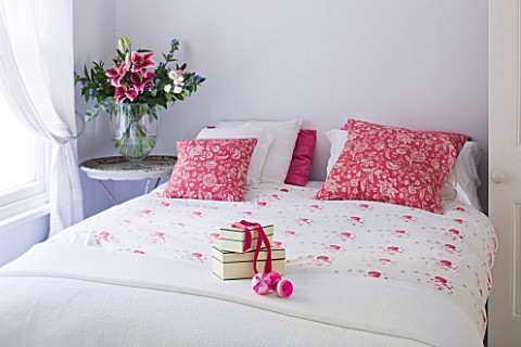 DESIGNER_JACKY_HOBBS__LONDON__WHITE_BEDROOM_AT_CHRISTMAS_WITH_PRESENT_ON_BED_AND_RED_PILLOWS
