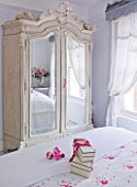 DESIGNER JACKY HOBBS  LONDON - WHITE BEDROOM AT CHRISTMAS WITH PRESENT ON BED AND MIRROR FRONTED WARDROBE