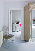 DESIGNER JACKY HOBBS  LONDON - WHITE BEDROOM AT CHRISTMAS WITH MIRROR FRONTED WARDROBE AND VIEW THROUGH TO BATHROOM BEYOND