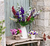 THE GARDEN AND PLANT COMPANY  HATHEROP CASTLE  CIRENCESTER  GLOUCESTERSHIRE: JUG WITH LUPINS  HESIAN POT OF DOUBLE COSMOS  PALE OF MIXED SWEET PEAS